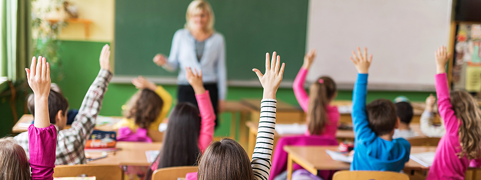 students in classroom raising their hands to answer question