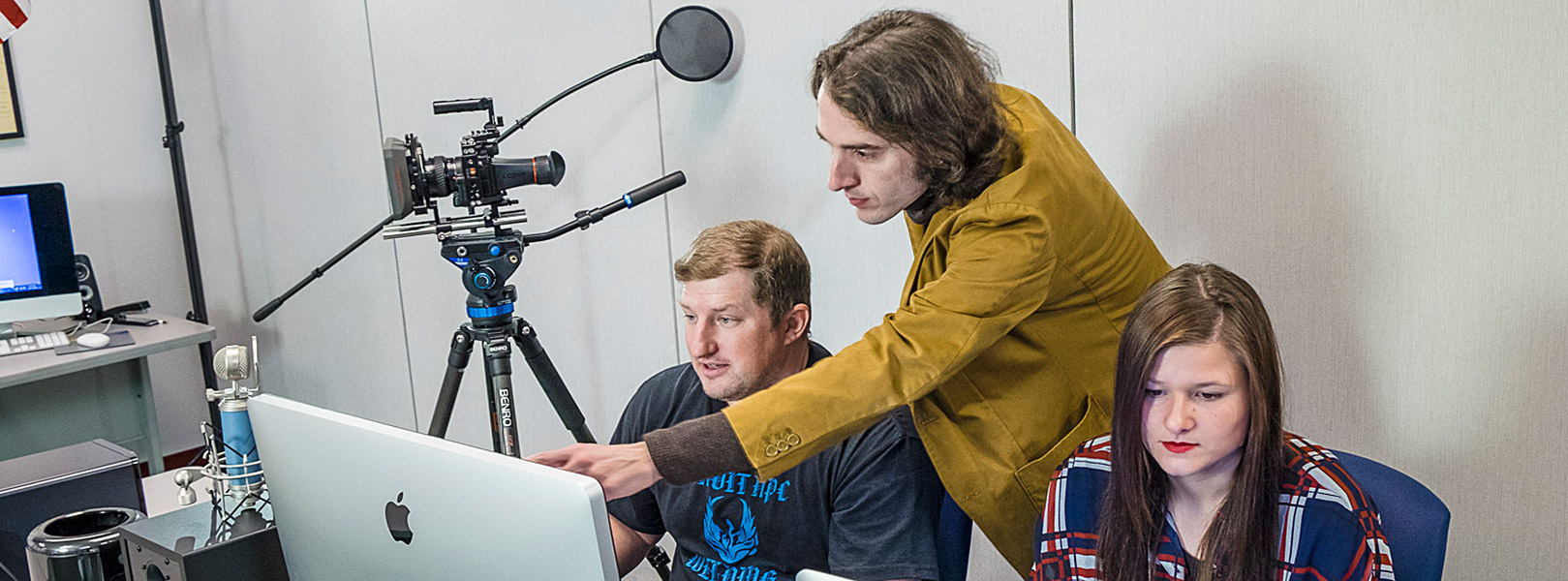 instructor helping student edit film on computer