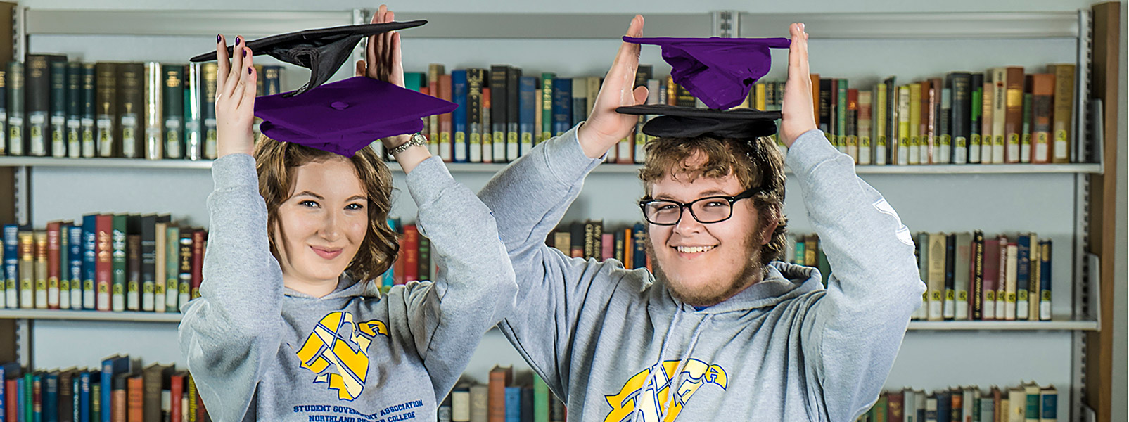 two students holding two graduation caps each