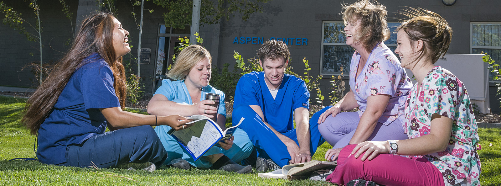 healthcare students sitting on campus lawn