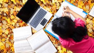 Girl studying on bed of fall leaves