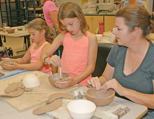 The Riesland family creates bowls for the Empty Bowls event.
