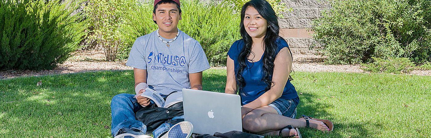 two high school students sitting on NPC lawn with laptop